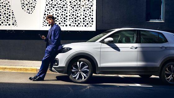 Eine Frau steht und schaut in die Kamera, im Hintergrund steht ein Volkswagen Modell
